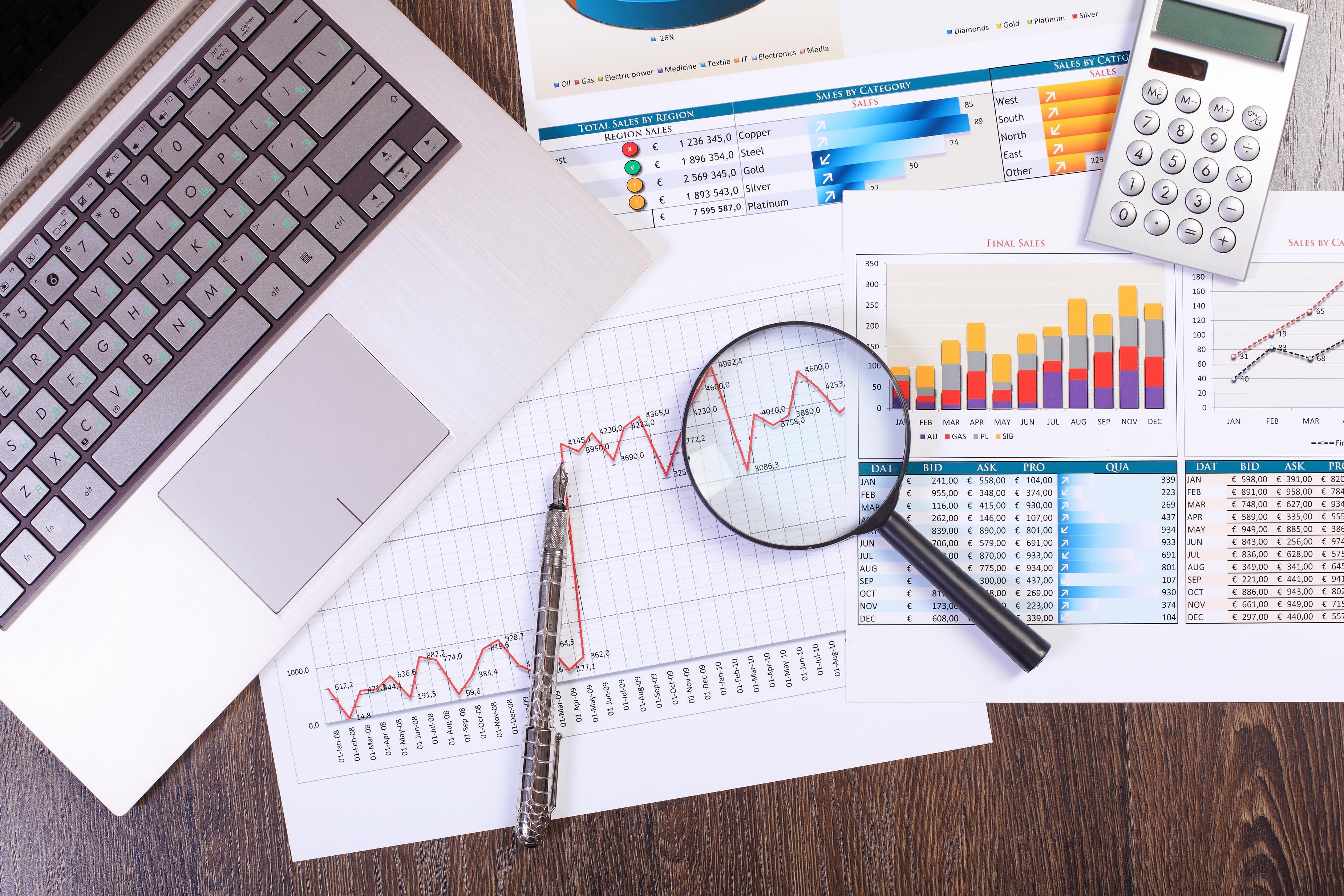 mesa com papeis e computador usados na engenharia econômica